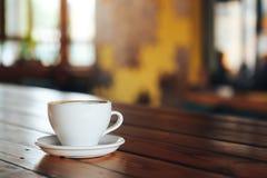 Café quente no copo branco na tabela de madeira Xícara de café branca em uma tabela de madeira em um café Fotos de Stock Royalty Free