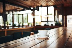 Café quente no copo branco na tabela de madeira Xícara de café branca em uma tabela de madeira em um café Imagem de Stock