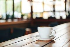 Café quente no copo branco na tabela de madeira Xícara de café branca em uma tabela de madeira em um café Fotografia de Stock Royalty Free