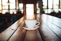 Café quente no copo branco na tabela de madeira Xícara de café branca em uma tabela de madeira em um café Imagens de Stock Royalty Free