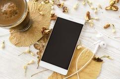 Café quente, tabela do telefone com folhas fotos de stock royalty free