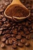 Café râpé dans la cuillère sur le fond rôti de grains de café Photographie stock libre de droits