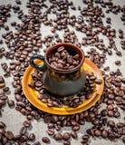 Café rústico Taza de café de la arcilla y granos de café asados Foto de archivo libre de regalías