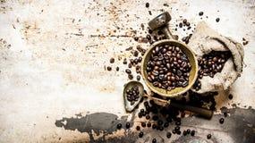 Café rôti dans un mortier avec le pilon et le sac photo stock