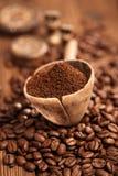 Café rallado en cuchara en los granos de café asados Fotos de archivo