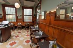 Café retro tradicional wating para los visitantes alrededor de las tablas de madera, espejos, estilo artístico imagen de archivo