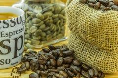Café roasted fresco e resto do feijão verde na garrafa pequena Fotos de Stock