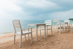 Café romántico con las tablas y las sillas blancas en la orilla de mar imagen de archivo