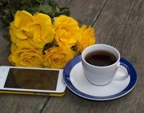 Café, rosas amarillas y el teléfono móvil en una tabla de madera Fotos de archivo libres de regalías