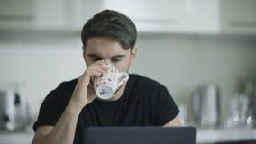 Café sério da bebida do homem que trabalha em casa Homem de negócio focalizado que trabalha no portátil video estoque