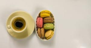 Café sólo delicioso en una taza de cerámica hermosa con los macarrones Foto de archivo libre de regalías