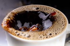 Café sólo derramado en una taza en una tabla negra Mala superficie de la bebida en el envase fotos de archivo