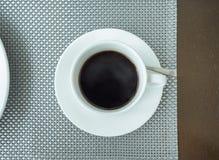Café sólo en la taza de cerámica blanca en la tabla Fotos de archivo libres de regalías