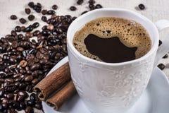 Café sólo en palillo de la taza y de canela y granos de café asados Imagen de archivo