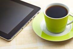 Café sólo en taza verde con la tableta del ordenador Foto de archivo