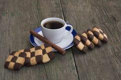 Café sólo en un platillo con una frontera azul y galletas a cuadros, una vida inmóvil Imagenes de archivo