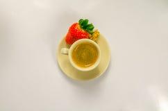 Café sólo en una taza de crema con la fresa jugosa Imagen de archivo libre de regalías