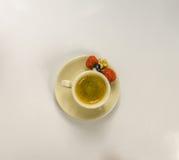 Café sólo en una taza de crema con la fresa jugosa Foto de archivo