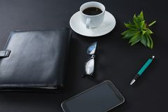 Café sólo, flora, pluma, gafas, teléfono móvil y organizador en fondo negro Fotos de archivo