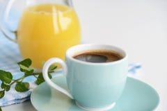 Café sólo fuerte en una taza azul clara en una tabla blanca con el zumo de naranja Fotografía de archivo