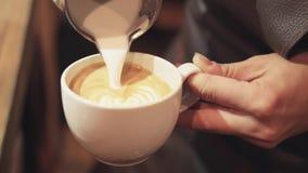 Café se renversant de barman avec du lait pour faire le latte d'art Le barman prépare le latte emportent dedans la tasse blanche, clips vidéos