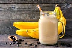 Café, smoothie de banane, scène contre le bois rustique photographie stock libre de droits