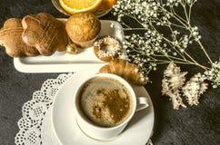 Café soluble dans les plats blancs de tasse avec des pâtisseries, sur une serviette de papier Image libre de droits