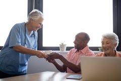 Café sonriente de la porción del trabajador de la atención sanitaria al hombre mayor que se sienta por el amigo Imágenes de archivo libres de regalías