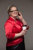 Café sonriente y de consumición de la mujer de mediana edad del negocio foto de archivo