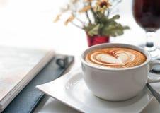 Café sur le bureau fonctionnant au cours de la réunion d'affaires avec l'art de Latte de forme de coeur d'amour images stock
