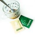 Café, tasse de café, sachets de crémeuse, paquets de sucre pour le petit déjeuner Images stock