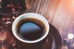 Café Taza de café y de habas asadas en el primer de madera de la tabla espresso imagenes de archivo