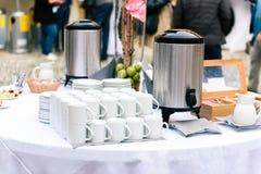 Café, tazas en la tabla del abastecimiento en la conferencia o banquete de la boda Imagenes de archivo