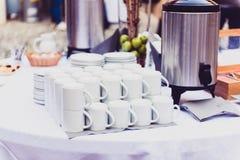 Café, tazas en la tabla del abastecimiento en la conferencia o banquete de la boda Fotos de archivo libres de regalías