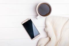 Café, teléfono y suéter hecho punto en la tabla blanca Imágenes de archivo libres de regalías