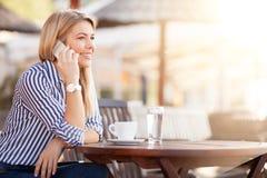 Café telefonando e bebendo da mulher ocupada bonita da manhã imagens de stock