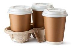 Café três take-out. Dois copos no suporte. Imagem de Stock
