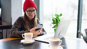 Café travaillant et potable de belle jeune femme dans un café banque de vidéos