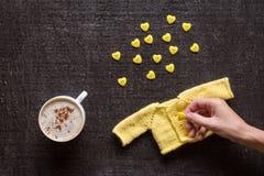 Café, tricotage et main avec le bouton sur le noir Photo stock