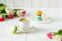 Café, tulipes roses et blanches et macarons sur la table en bois blanche Image libre de droits