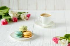 Café, tulipes roses et blanches et macarons sur la table en bois blanche Photographie stock libre de droits