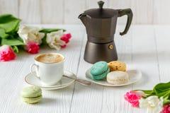 Café, tulipes roses et blanches et macarons sur la table en bois blanche Images libres de droits