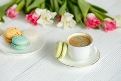 Café, tulipes roses et blanches et macarons sur la table en bois blanche Photo stock