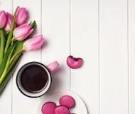Café, tulipes roses et macarons sur la table en bois blanche Photos stock