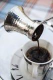 Café turco de derramamento a um copo Fotografia de Stock