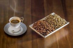 café turco quente do copo branco e grãos de café dispersados Imagem de Stock