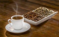 café turco quente do copo branco e grãos de café dispersados Fotografia de Stock