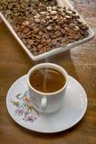 café turco quente do copo branco e grãos de café dispersados Fotos de Stock Royalty Free