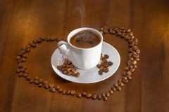 café turco quente do copo branco e grãos de café dispersados Foto de Stock Royalty Free