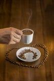 café turco quente do copo branco e grãos de café dispersados Imagem de Stock Royalty Free